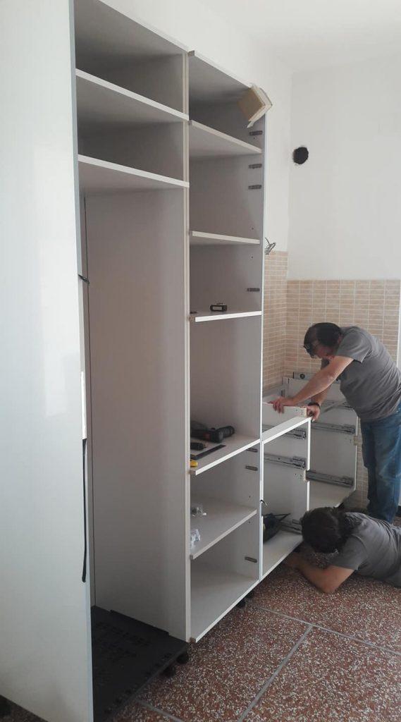 Cucina componibile su due pareti finitura laccato bianco lucido. Top in quarzo grigio.